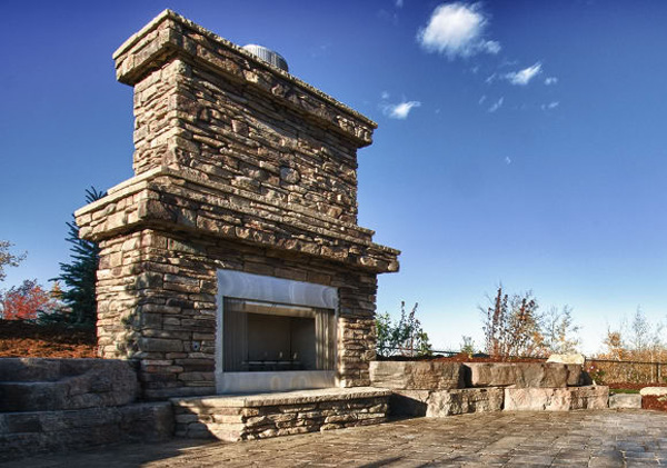 Outdoor stone fireplace feature in this yard