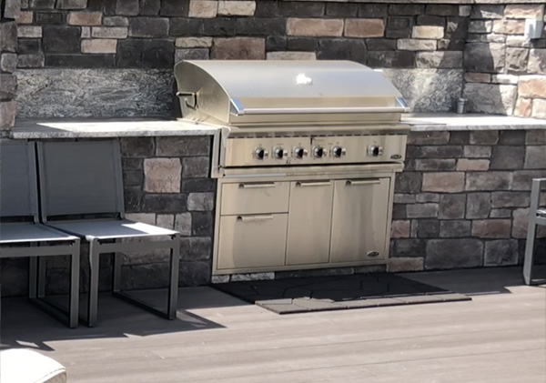 Outdoor kitchen area of deck with stone countertops.
